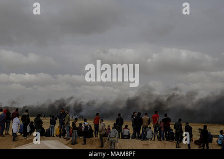Palestinian protesters watch clouds of smoke as they rise from burnt tyres, to distract Israeli troops, during clashes along the borders between Israel and Gaza, east of Khan Yunis, southern Gaza Strip, 03 April 2018. Photo: Mohammed Talatene/dpa - Stock Photo