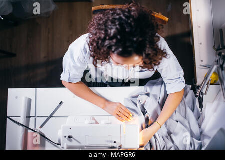 high view shot of dressmaker sitting in front of sewing machine and working - Stock Photo