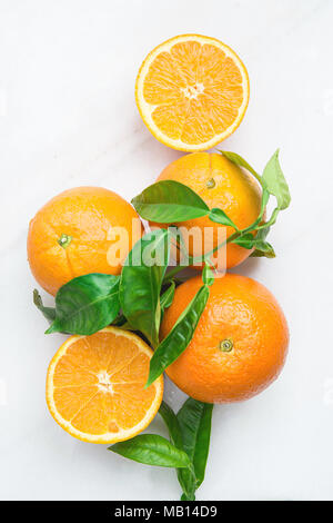 Bunch of Ripe Juicy Whole and Halved Orange with Green Leaves on White Stone Marble Table. Vitamins Healthy Diet Summer Detox Vegan Tropical Fruits Co - Stock Photo