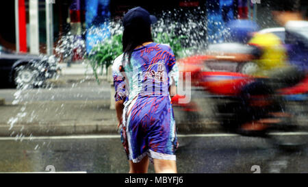 Passengers on a passing motorbike are splashed with water during Songkran, 2001 in Bangkok, Thailand. - Stock Photo