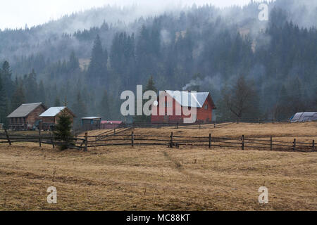 Mountains village houses with forest hills in mysterious smoke on the backside - Stock Photo