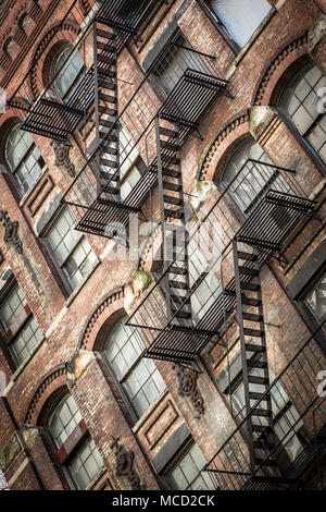 Fire escapes on a brown stone apartment building in Manhattan, New York City. - Stock Photo