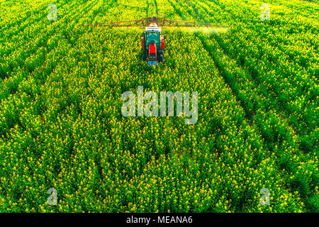 Aerial view of farming tractor plowing and spraying on field. - Stock Photo