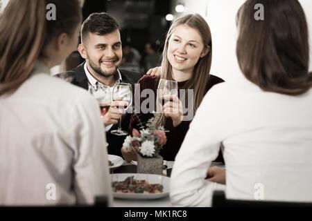 Friends are having dinner in the restaurante indoor. - Stock Photo