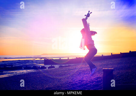 LONDON, ENGLAND - FEBRUARY 17 : Excited young child leaping and jumping from the wave breakers  (toy in hand) along the shingle beach as the sun goes down. Bexhill and De La Warr Pavilion (Magnum Photo Exhibition) Bexhill-on-Sea, East Sussex. 29 November 2015. United Kingdom. - Stock Photo