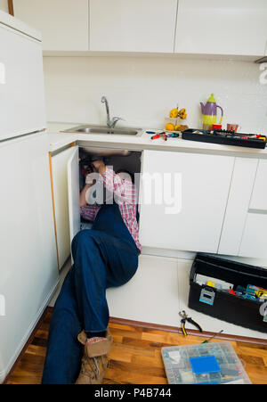 Worker repairs the leakage problem in the kitchen sink Stock Photo ...
