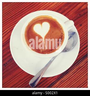 Looking down on a coffee drink in cup with a spoon and a decorated garnish - Stock Photo