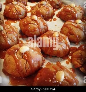 Peanut butter cookies drizzled with toffee sauce - Stock Photo