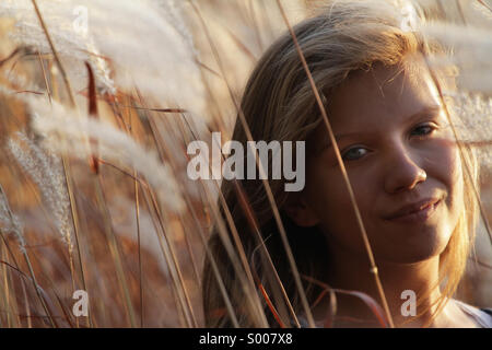 A young woman walks through Autumn grasses. - Stock Photo