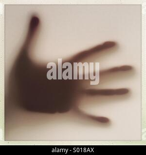 Hand silhoutte on window - Stock Photo
