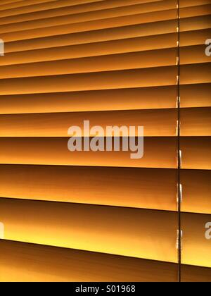 Interior photograph of a closed venetian blind in warm sunlight. - Stock Photo