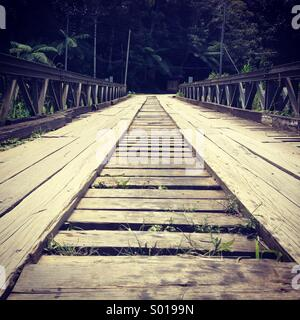 An old wooden bridge still used today for crossing a river to the otherside. - Stock Photo