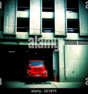 A red dump truck is parked in the entry to a parking garage - Stock Photo