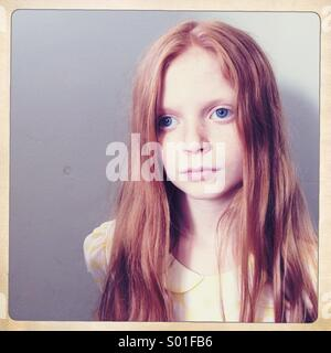 Red haired girl stares blankly off camera with a plain grey background - Stock Photo
