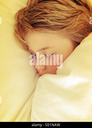 Boy sleeping under white sheets - Stock Photo