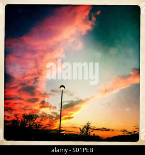 Lone street lamp against a vibrant sunset sky. - Stock Photo