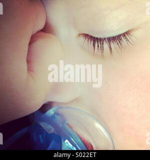 Close-up of a baby boy sleeping with a blue dummy soother in his mouth. - Stock Photo