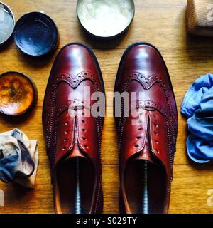 A pair of brown wingtip brogues lined up after a polish and cleaning work, surrounded by polishing tools - Stock Photo
