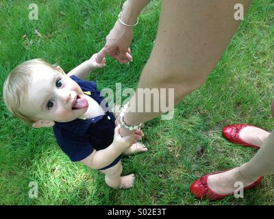 Baby boy's first steps with mom in summer. - Stock Photo