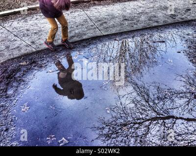Boy and trees reflected in puddle of water - Stock Photo