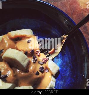 Close-up of fork sticking into blue bowl of banana slices, peanut butter, cacao nibs, on chopping block in dappled - Stock Photo