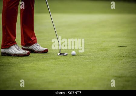 Golf player at hole - Stock Photo
