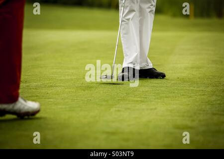 Golf players at hole - Stock Photo