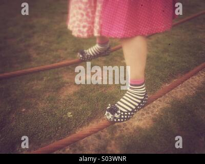 Young girl's feet balancing on tightropes. - Stock Photo