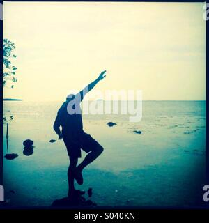 Man balancing on rock - Stock Photo