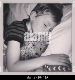 Sleeping boy with teddy bear. - Stock Photo