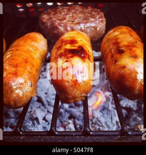 Three sausages and a burger cooking on a barbecue - Stock Photo