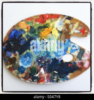Colourful artists oil paint palette on white background - Stock Photo