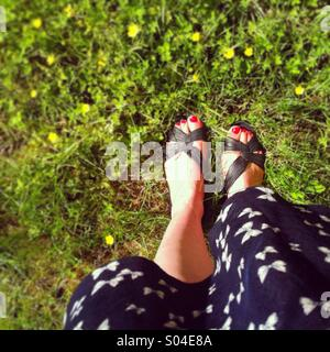 Looking down at feet in sandals and a summer dress standing on a LAN with small yellow flowers - Stock Photo