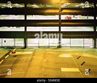 Red car in empty parking garage - Stock Photo