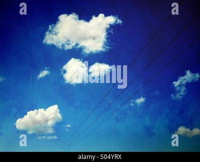 Pylon wires and white clouds against blue sky - Stock Photo