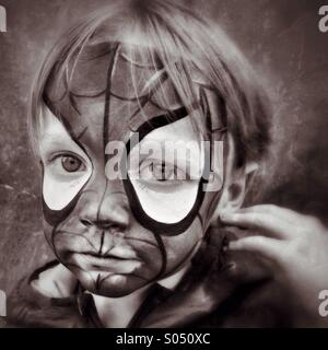 Sad Spidey. Boy unhappy in Spider-Man face makeup - Stock Photo