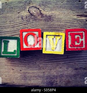 It's a photo of two wood cubes toy with letters that form the word LOVE - Stock Photo