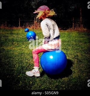 Young girl bouncing on space hopper - Stockfoto