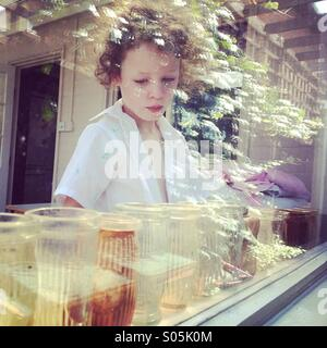 Thoughtful girl behind window with reflections - Stock Photo