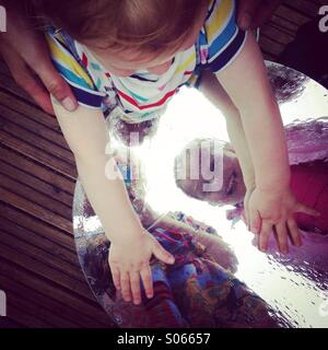 Kids playing with reflections on a table outside in summer. - Stock Photo