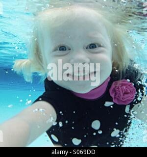 Young girl smiling as she swims towards camera underwater. - Stock Photo