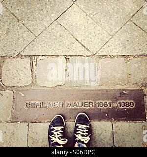 Berlin Wall memorial stones in pavement with feet - Stock Photo