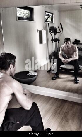 Fitness - Muscular man in a gym sitting in front of a mirror - Stock Photo