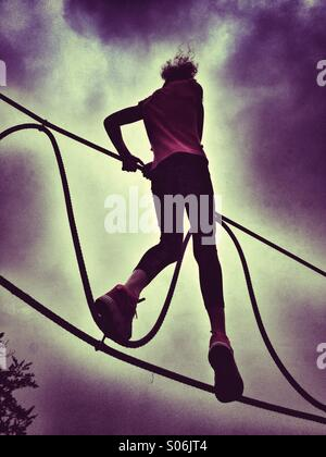 Girl balancing on rope walk - Stock Photo