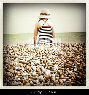 Girl In Hat, Sitting On Pebbled Beach - Stock Photo