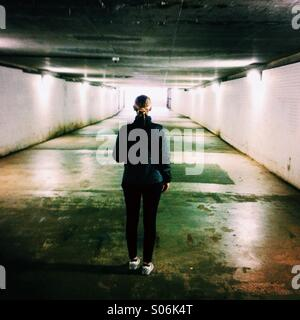 A young woman walks alone in an underpass. - Stock Photo