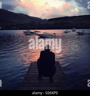 A crouching man looking out over a Scottish loch at sunset - Stock Photo