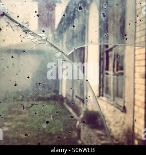 An old facade viewed through a broken glass - Stock Photo