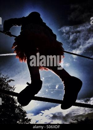 Young girl balancing on rope walk - Stock Photo