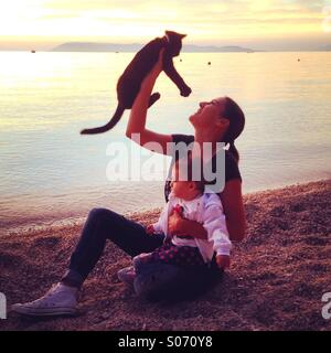 Mom holding cat and baby near the sea at beach - Stock Photo